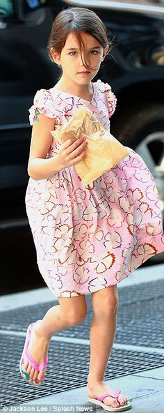 Pretty in pink: Suri was bright and colourful for the outing, wearing a floral pink dress teamed with matching flip-flops