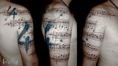 Large shoulder sheet music water color tattoo
