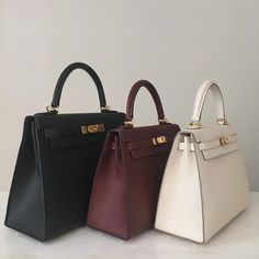 Hermes Kelly Sellier 28cm and 25cm pictured in black, Rouge H, and Craie Epsom leather with gold hardware.