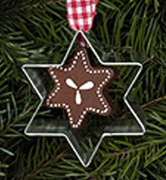 Charming Christmas ornament, combining a wooden gingerbread (lebkuchen) cookie in the shape of a star with a made in Germany star-shaped metal cookie cutter - hung with a red gingham bow. The cookie c