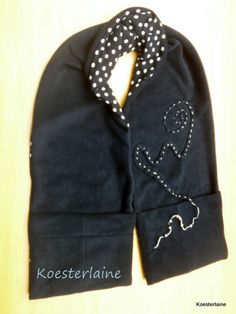 """Abrazo (gevoerde sjaal met 2 zakken) Deze dubbelzijdige sjaal heet Abrazo (""""omarming"""" in het Spaans). Hij is van zwarte fleece en gestipt tricot met applicatie . De zwarte kant heeft 2 zakdelen aan het uiteinde. Hierin blijven handen warm. Ook kun je er dierbare spulletjes in stoppen of juist een streelzacht sjaaltje."""