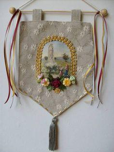 Estandarte Nossa Senhora de Fátima <br>Feito em tecido com flores e fitas <br>Produto artesanal , sujeito á variações <br>Podemos fazer com outros motivos religiosos <br>Temos vários modelos <br>Consulte - nos