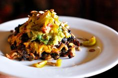 Mexican Lasagna topped with guac, pickled jalapeno, and toasted sunflower seeds