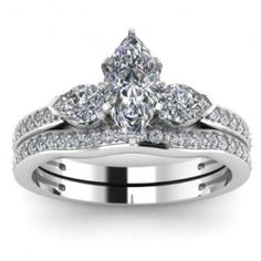 Marquise 3 Stone Diamond Engagement Ring Wedding Set - One of the most beautiful we've reviewed comes this Marquise 3 Stone Diamond Engagement Ring Wedding Set in 14k White Gold in a Pave & Prong setting with a White Marquise cut center stone with 2 White Pear cut stones with 42 round accent stones on the ring & band. The Marquise 3 Stone engagement set comes with an SI3 in clarity with a G in color & the gem weight is equal to 1.50 carats. The diamonds are 100% natural…