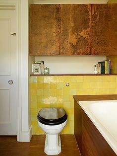 Homes - In With The Old: bathroom with yellow tiling and copper cabinets