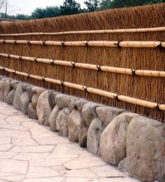 A completed Daimyo fence set above a stone knee wall. An additional horizontal bamboo of smaller diameter is added to help accentuate the broom effect. Additional half-culms are added to the top of the fence. Fasteners are hidden with decorative black pal Brick Fence, Concrete Fence, Front Yard Fence, Farm Fence, Bamboo Fence, Fenced In Yard, Rustic Fence, Fence Stain, Fence Art