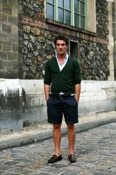 Shop this look on Lookastic:  https://lookastic.com/men/looks/cardigan-long-sleeve-shirt-shorts-loafers-belt/12220  — White Long Sleeve Shirt  — Dark Green Cardigan  — Black Leather Belt  — Navy Shorts  — Dark Brown Leather Loafers