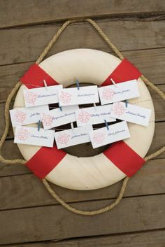 Michaels.com Wedding Department: Nautical Place Cards Greet your guests at the reception with cleverly displayed place cards or escort cards. This display was created using the Gartner Studios pearl white border printable place cards. The cards were stamped using red ink and a coordinating design and are hung on baker's twine that was wrapped around the nautical display. Courtesy of Gartner Studios®