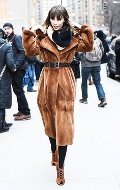 A tan fur coat is paired with a fur infinity scarf, brown belt, black tights and tan lace-up open-toed booties