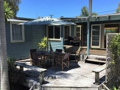 Classic Kiwi Bach with large sunny deck. Palm Beach is a lovely Kiwi bach located within the golden circle of Mangawhai Heads. Situated on a private sunny s. New Zealand Houses, Holiday Accommodation, Stay The Night, Exterior Lighting, New Builds, Outdoor Entertaining, Kiwi, Palm Beach, Deck