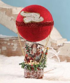 "Fly away with Santa and his magical hot air balloon, wishing everyone a Merry Christmas! - 10"" x 4.25"". - Pressed paper, glitter, woven basket and flocked Styrofoam. - Bethany Lowe Vintage Christmas C"