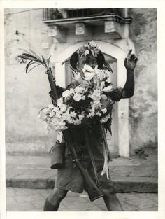 1943-  Flower-bedecked by the civilians of Catania, a British soldier makes his way down the town's main street with even his rifle sprouting a posy.