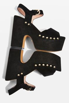The sky's the limit with these towering black platform sandals. This striking style features an open toe, gold-tone stud detailing and an adjustable ankle strap. Wear them to make your grand entrance at your next party.