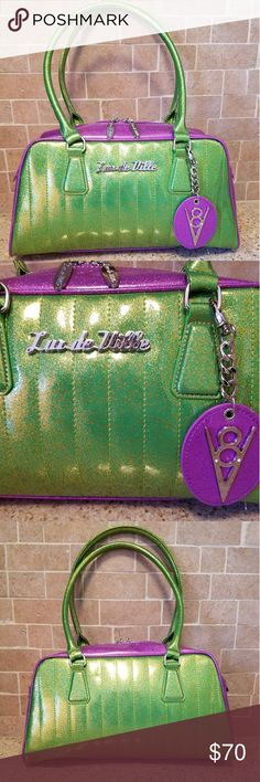 NWOT Lux De Ville V8 Gorgeous bag! Green with gold flecks and purple trim. Tons of room inside. Zippered pocket and two additional pockets inside.   Dimensions: 14 W x 8H x 5 deep. Strap drop is 9 inches. Lux De Ville Bags