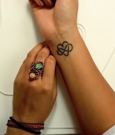 Cuore e simbolo infinito tatuati sul polso