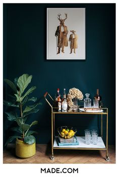 Cocktail trolley in brushed brass contrasted with deep, bold dark walls. Step inside the South West London Home of Sommer Pyne to see more interior inspiration.
