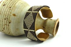Beautiful loom woven beaded bracelet over a brass cuff. The woven bracelet is made with antique metallic black and silver 11/0 glass seed beads.