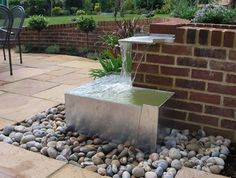 The existing slope within the garden necessitated the construction of a curved brick retaining wall enclosing the main terrace.  Using the level change to provide an unusual water feature.   JJ Designs
