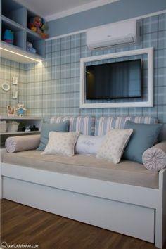 Cama de babá com enxoval bege e almofadas coloridas, papel de parede listrado nicho iluminado com enfeite.