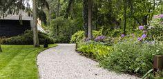 Exclusieve villatuin - oprit van grind met strak gazon en bloemrijke schaduwborders.
