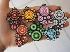 Seven quilled tight coil pendants in various colors. July 2014.