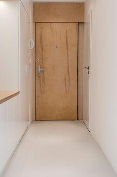 Vchodová hala je převážně bílá. Bílé přírodní linoleum Armstrong i bílé vestavné skříňky jsou doplněny parapetem a vchodovými dveřmi z březové překližky natřené voskovým olejem - ProŽeny.cz