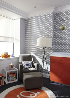 Love this modern geometric accent wall in this gray and orange nursery!