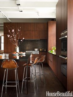 Vintage Charlotte Perriand stools are gathered at the corner of the island in a New York City kitchen designed by Elena Frampton of Curated, which is topped with Absolute Black granite. The dark, iridescent backsplash is made of New Gunmetal tile by Heath Ceramics.