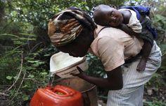 La joven suazi Zanele Dlamini, con su hijo de 13 meses a la espalda, mientras llena un bidón con agu... - EFE