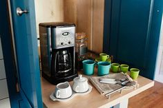 A pull-out shelf inside a cabinet next to the fridge houses a station always-ready for early morning coffee. Photo: Joe Dodd