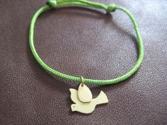 Paloma  hand made 18k gold dove charm on nylon string by ShaktiEllenwood, $175.00.  The dove is a symbol of peace, innocence and compassion. The green string represents abundance and creativity.
