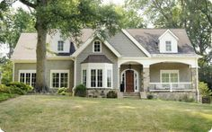 Warm gray, creamy white, stained door, and stone accent...this house has it all!