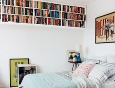 rise and shine Bookshelves that hang from the ceiling make use of wasted space, emphasize a room's height, and free up the wall and floor beneath them.