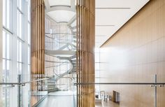 GSA Region 8's U.S. Courthouse Annex in Salt Lake City, UT. The interior features wood paneling and white oak floors that temper the glass and aluminum characteristics of the exterior. A circular glass staircase that connects the first three floors is a focal point in the entry atrium. LEED Gold 2015.
