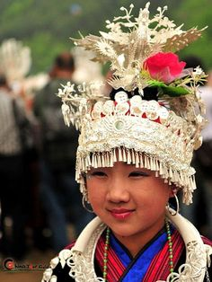 Chinese The young Miao girl is dressed up nicely with the headdress, hairpins, neck-rings, chest locks, and lots of accessories.