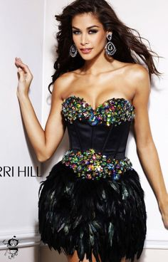 650 Sherri Hill 2886 is a fancy type of dress with a very unique appeal!  This short dress has a skirt that is covered in the biggest trend right now...feathers!  It has a strapless corset bodice with a sweetheart neckline.  Large multicolored rhinestones cover the bust and waistline.  It is available in the Black/Multi.