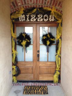 MIZZOU fans...Mississippi style! This is my front door decorated for football season. Mesh around the doorway tied with black & white polka dot grosgrain ribbon. Wreaths made of tulle. Letters are from Hobby Lobby - hand painted & glittered them myself. Coconut fiber, zebra print door mat is also from Hobby Lobby. I hand-painted the neutral stripes with acrylic paint. May add lights in the mesh next year. :)