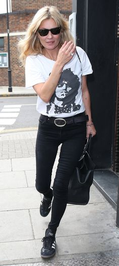 Kate Moss in a tailored, graphic tee, black skinny jeans, a ladylike tote, and three-stripe Adidas trainers