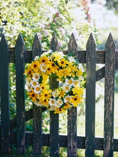 "Love the daisy-and-black-eyed-susans wreath against the rustic picket gate.. So ""summertime in the country"". :)"