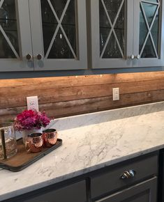 Rustic wood backsplash for bar area. Grey cabinets and warm wood backsplash with lighting. White polished stone countertops and warm wood backsplash for a rustic look in kitchen. Kitchen Redo, Rustic Kitchen, New Kitchen, Shiplap In Kitchen, Rustic Backsplash Kitchen, Kitchen Ideas, 1960s Kitchen, Ranch Kitchen, Colonial Kitchen