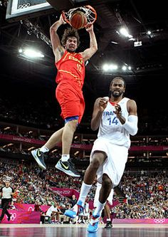 Sergio Llull #12 of Spain goes up for a dunk in front of Ronny Turiaf #14 of France in the Men's Basketball game.