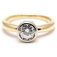 An 18 karat yellow gold bezel set mounting containing a 0.25 carat modern round brilliant cut diamond.