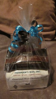 Baby Shower Game Prizes - treat bag of local coffee shop's yummy hot cocoa mix, a gourmet chocolate, and a sample of Camille Beckman lotion.  Bags are tied with ribbons the color of the nursery.