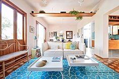 Quer prolongar a sensação gostosa das férias? Na @revistacasaclaudia de dezembro você encontra 30 ideias para levar o estilo despojado das casas do litoral para o décor urbano. Nesta sala, assinada pelos arquitetos do @amstudio_arq, o tapete azul, o sofá e as mesinhas brancas criam uma decoração fresh. : André Weigand #nasbancas #arquiteturabrasileira #arquitetura #decoração #home #house #décor