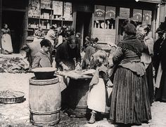 A view of Sandgate which shows a group of women and children surrounding a woman who is gutting a fish. Another group of women are sorting through bundles of clothing outside the Horse Inn.