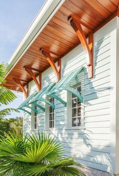 Horizontal siding colorful Bahama shutters a beautiful wood soffit and decorative wood brackets create an island-inspired feel at this Florida home. Tropical foliage enhances the design.