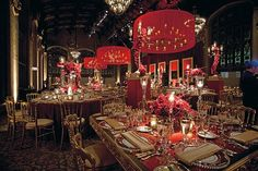 A bounty of red and merlot roses set beneath custom wrought iron chandeliers with sheer drum shades housing pillar candles.