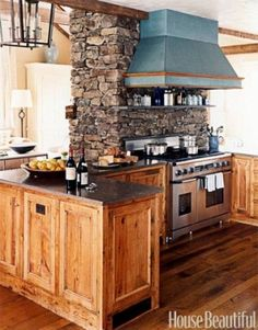 Kitchen with stone chimney I love the asymmetrical stones, and how it separates the two room, while bringing both of the rooms into one.