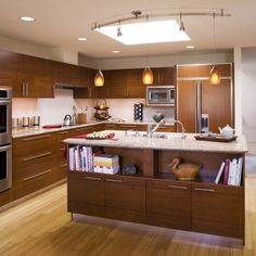 : Small Asian Kitchen Idea Arranged In G Shape With Curved Track Lighting Pendants Installed Above Island With Bookcase