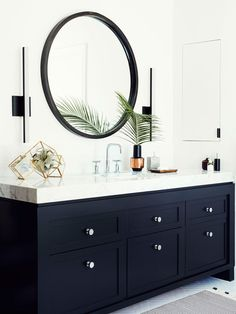 """The Vanity """"We wanted to keep within the house's East Coast architectural influence,"""" says Quattrone, who created a modern interpretation of Shaker-style millwork for two adjacent vanities. To mimic the look of a high-end countertop, the designers sourced a less expensive ¾-inch marble slab. """"We mitered the corners and bookmatched the edges to give the illusion of a three-inch-thick surface,"""" says Sanders. The slim profile of the Y Lighting LED sconces, which slide up and down for optimal…"""